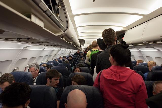 cestující v letadle sedí i procházejí uličkou.jpg
