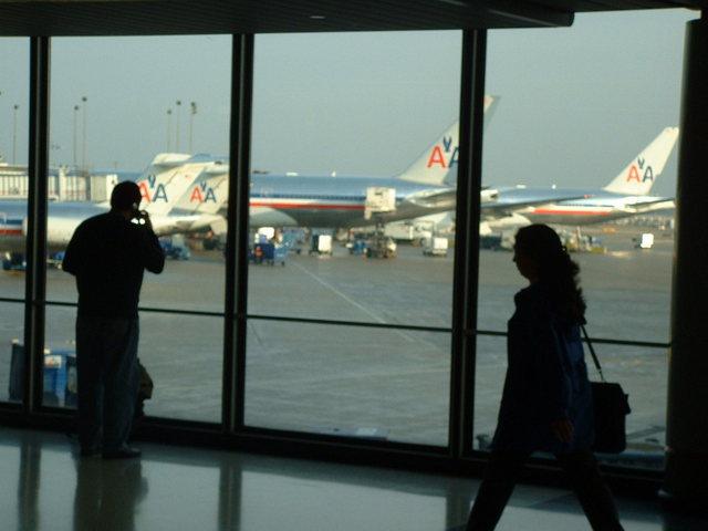 lidé v letištní hale a pohled na letadla.jpg