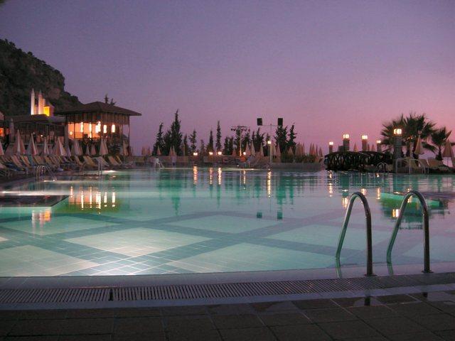 bazén na dovolené, když se stmívá s plážovými deštníky a lehátky.jpg