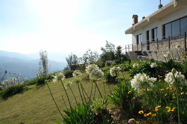 zahrada v popředí s bílými květy, s domem a krásným výhledem.jpg