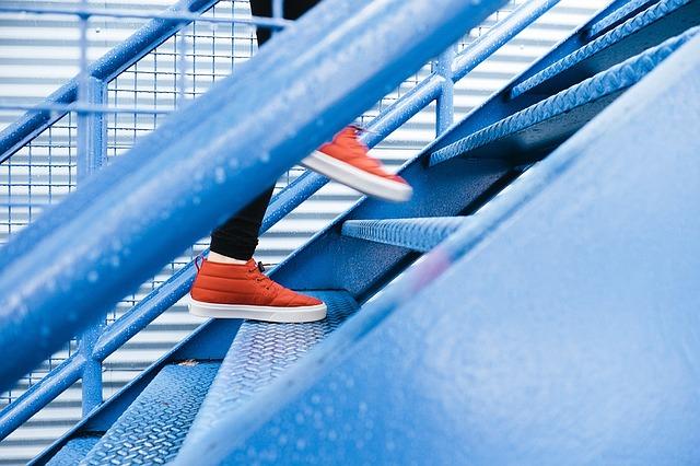 detail nohou člověka stoupajícího po ocelovém schodišti