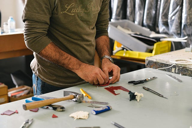 muž pracující v garáži, jdou mu vidět ruce a zelená mikina, stojí u stolu s různými věcmi a nářadím