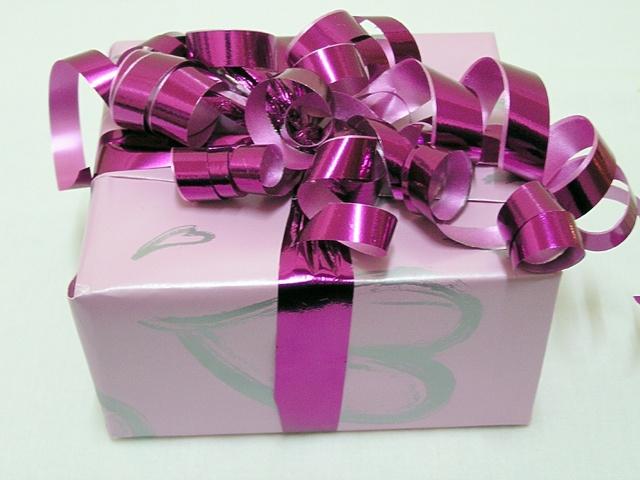 velký dárek s fialovou mašlí, nazdobený
